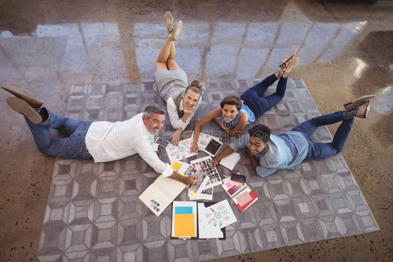 大角度观点的说谎在地毯的商人,当工作在创造性的办公室时 免版税库存照片