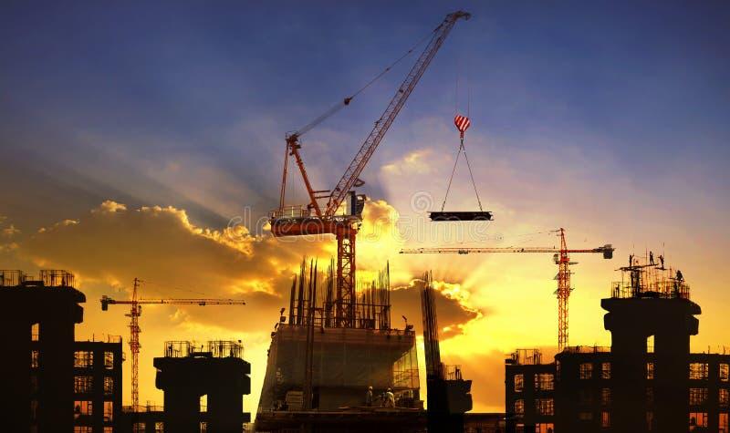大起重机和楼房建筑反对美丽的暗淡的天空 免版税库存图片