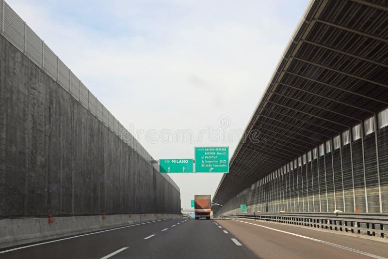 大路信号在意大利机动车路去到米兰或在地平线上方 免版税库存图片