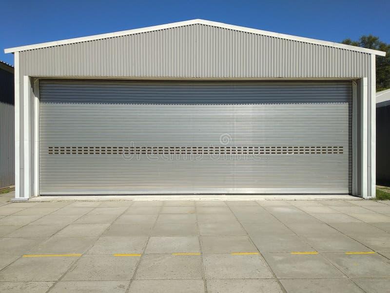 大车库仓库入口的滚动快门门与水泥封锁的地板,产业与天空蔚蓝的大厦背景的 免版税库存图片