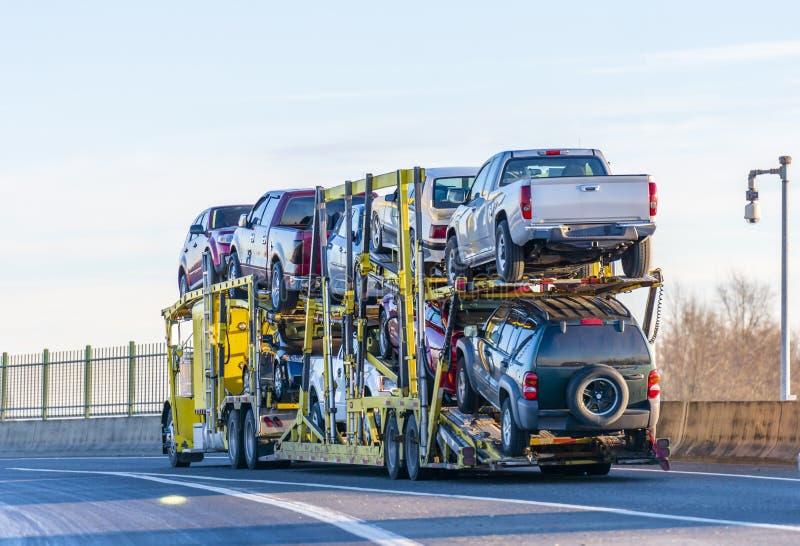 大运输在两个水平半拖车的船具黄色半汽车搬运工卡车汽车驾驶在天桥路 库存照片
