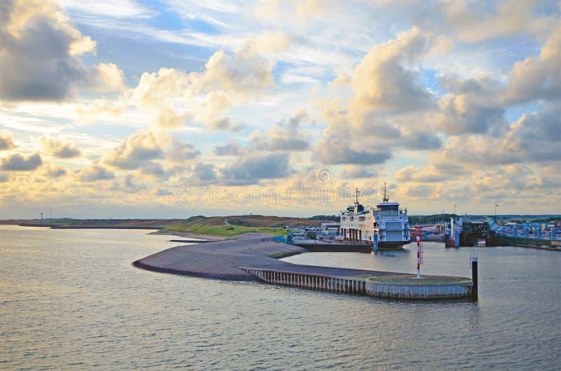 大退休的双结束passanger,并且由公司TESO的载汽车轮船在港口''在日落的t Horntje'叫'Schulpengat' 免版税库存照片