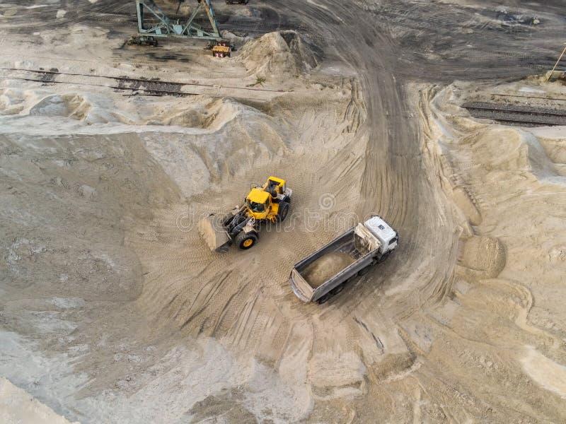 大重的轮子装载者装载的沙子到在沙坑的翻斗车里 重的工业机械概念 库存照片
