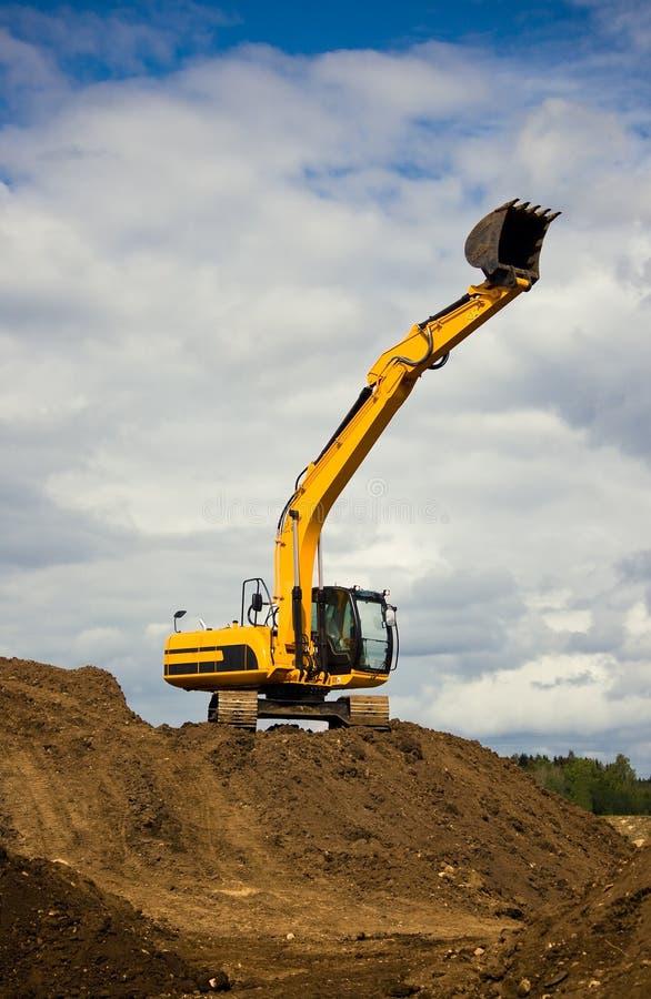 大量橙色挖掘机到达天空 库存图片