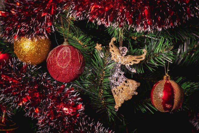 大金子和红色闪烁球和玻璃天使圣诞节的关闭在树 免版税库存图片