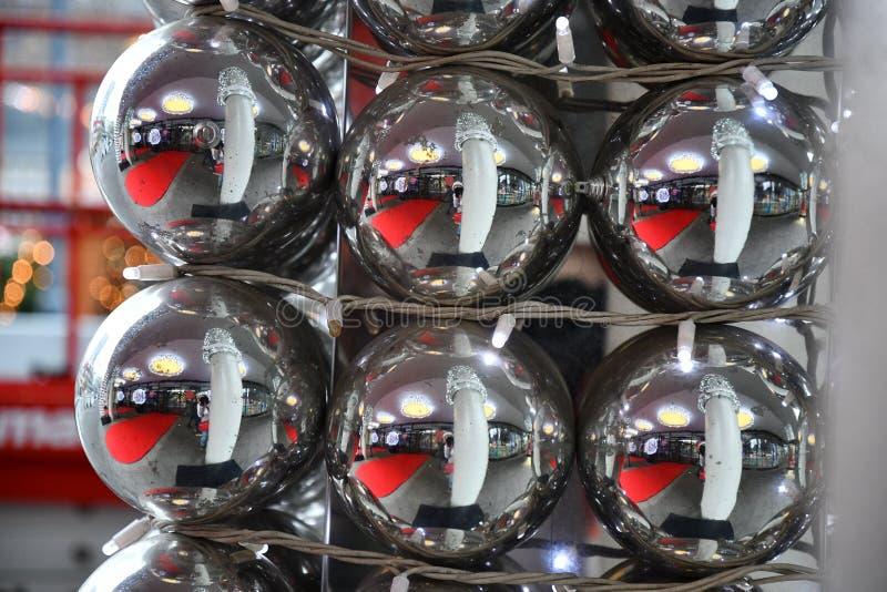 大镜子银色圣诞节装饰品特写镜头最小的样式圣诞节装饰  在许多发光的玻璃球的反射 免版税库存图片