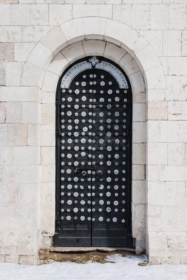 大门在一个古老石墙,锻铁门被锁的老金属 闭合的金属锁 库存照片