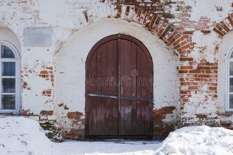 大门在一个古老石墙,锻铁门被锁的老金属 闭合的金属锁 图库摄影