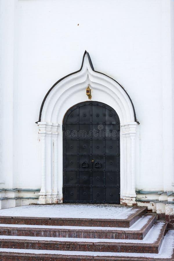 大门在一个古老石墙,锻铁门被锁的老金属 闭合的金属锁 免版税库存照片