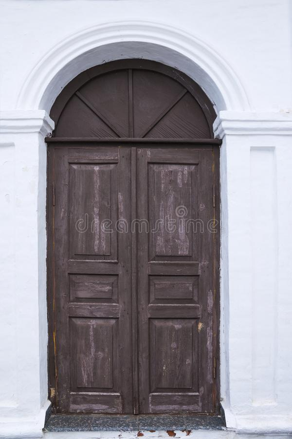 大门在一个古老石墙,锻铁门被锁的老金属 闭合的金属锁 免版税库存图片