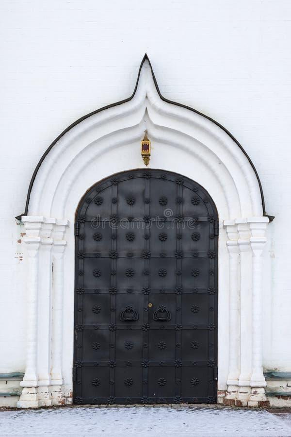 大门在一个古老石墙,锻铁门被锁的老金属 闭合的金属锁 库存图片