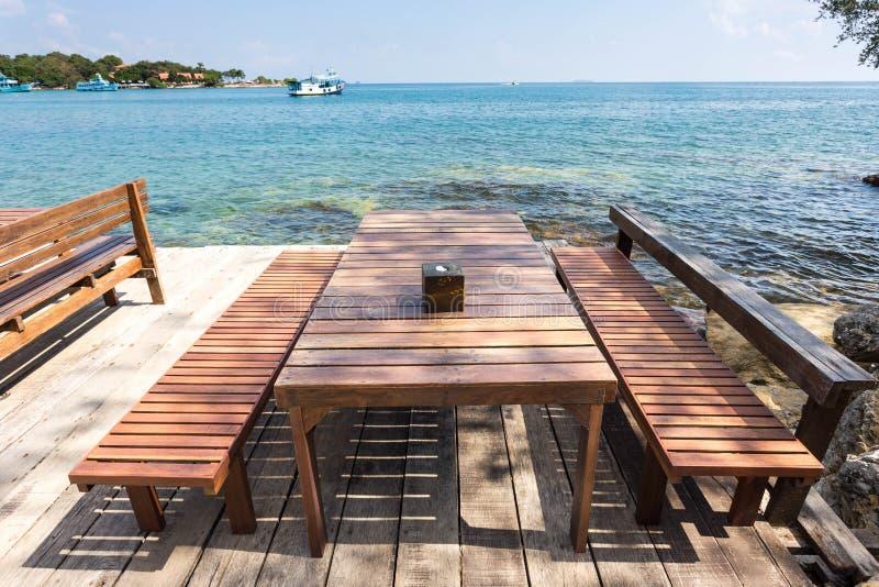 大阳台与室外木椅子和桌的海视图 库存照片