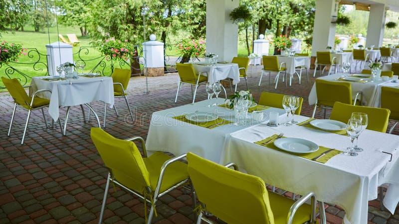 大阳台与桌和椅子人的,休闲的一个空的机关,没人的夏天咖啡馆 免版税图库摄影