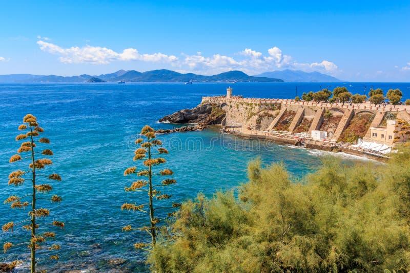 大阳台乔凡尼Bovio和Rocchetta灯塔的看法在皮奥恩比诺,托斯卡纳,意大利,在背景厄尔巴岛中 免版税库存图片