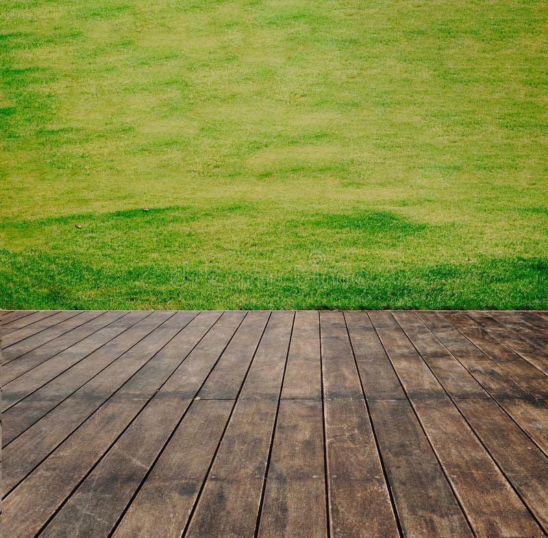 大阳台木地板纹理与绿色草坪的 免版税库存照片