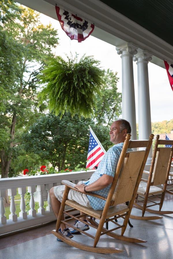 大阳台的坐的成人人与美国旗子 库存照片