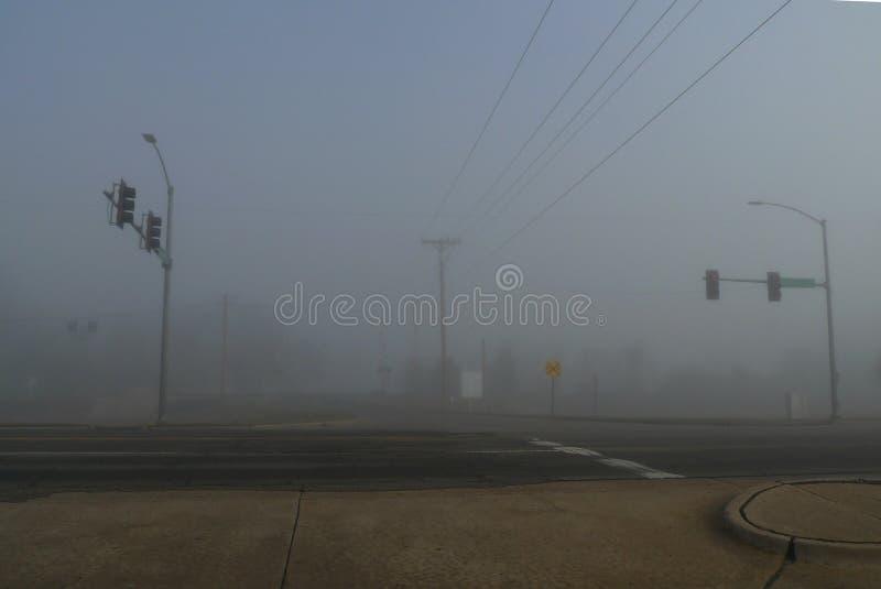 大雾和红绿灯有被修补的路的,平交道口 免版税库存照片
