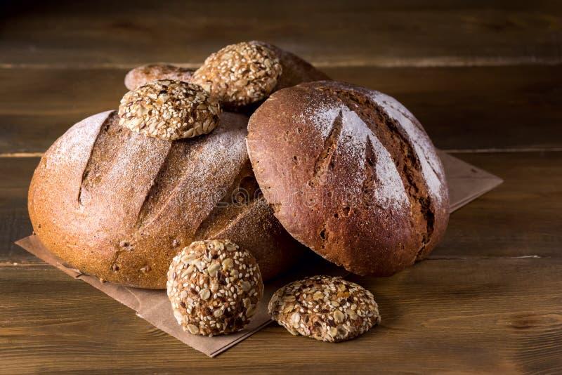 大面包新鲜的被烘烤的拉伊和在木面包拷贝空间纹理背景黑暗的照片品种的整个五谷面包品种  免版税库存照片