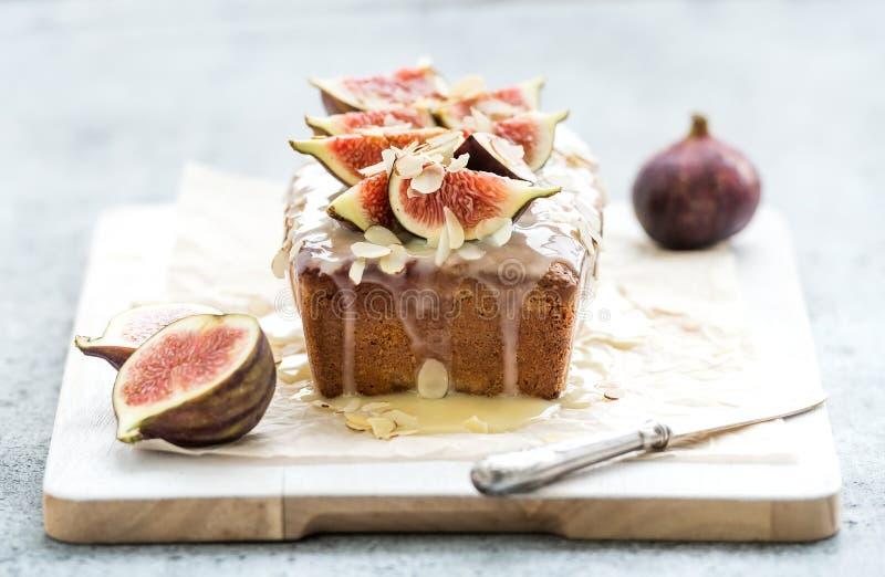 大面包蛋糕用无花果,杏仁和白色巧克力在木服务上在难看的东西背景,选择聚焦 免版税库存图片