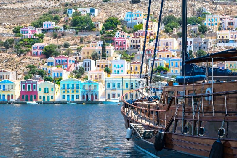 大风船和五颜六色的新古典主义的房子在锡米岛锡米岛海岛,希腊港口镇  库存照片