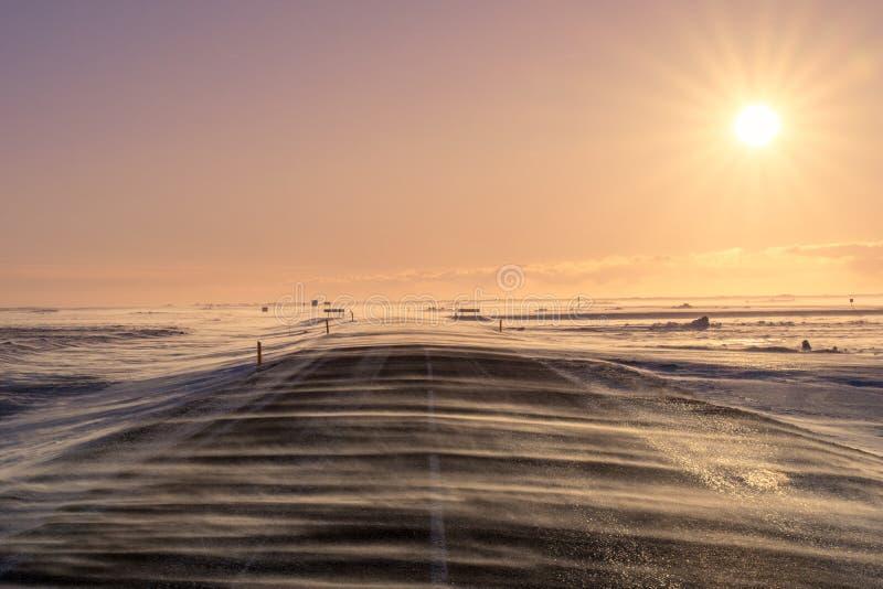 大风雪横跨路流动,几乎遮暗它在重的风期间在南冰岛 免版税图库摄影