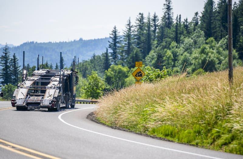 大驾驶在有绿色森林的弯曲道路的船具专业工业半汽车搬运工卡车 免版税图库摄影