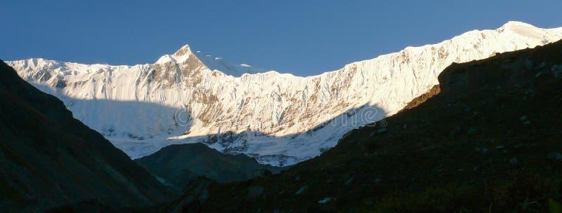大鹏努瓦尔和Tilicho峰顶-从Tilicho营地,尼泊尔的早晨全景 免版税库存图片