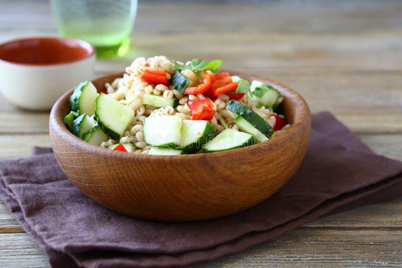 大麦米用黄瓜和胡椒在一个木碗 沙拉 库存图片