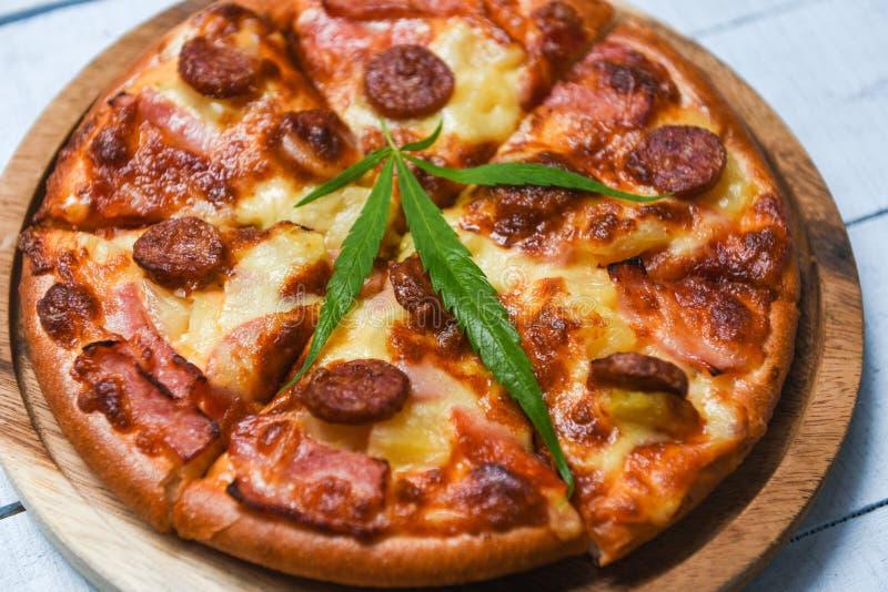 大麻在木盘子和辣椒蓬蒿叶子顶视图/可口鲜美便当意大利传统披萨奶酪的食物withPizza 免版税库存图片