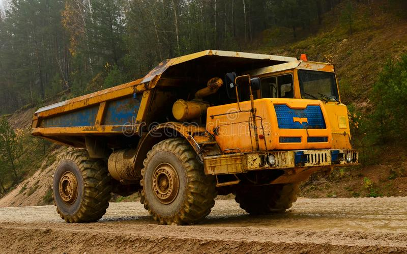 大黄色柴油猎物倾销者在工作 运输沙子和黏土的重的矿用汽车 库存图片