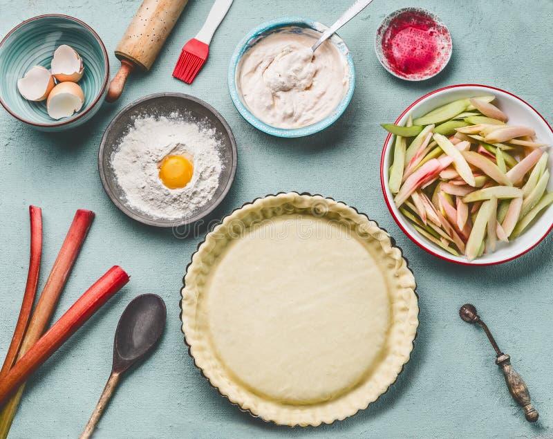 大黄饼准备 酸的烤盘用在厨房用桌背景的面团与滚针、面粉、鸡蛋和新鲜的红色大黄 免版税库存图片