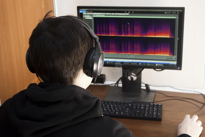 大黑耳机特写镜头的一个年轻人在计算机处理音乐轨道 创造在计算机上的音乐轨道 库存照片