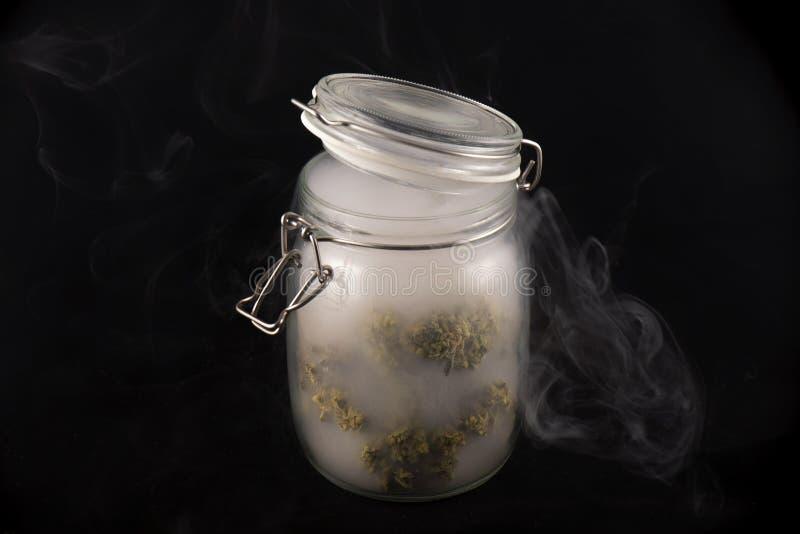 大麻发芽毛伊在一个玻璃瓶子的臭鼬张力有烟isol的 图库摄影