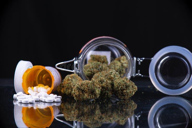 大麻芽和处方药片在反射性表面- 免版税库存照片
