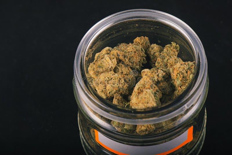 大麻芽& x28细节; 葡萄神strain& x29;在玻璃瓶子isolat 免版税库存照片