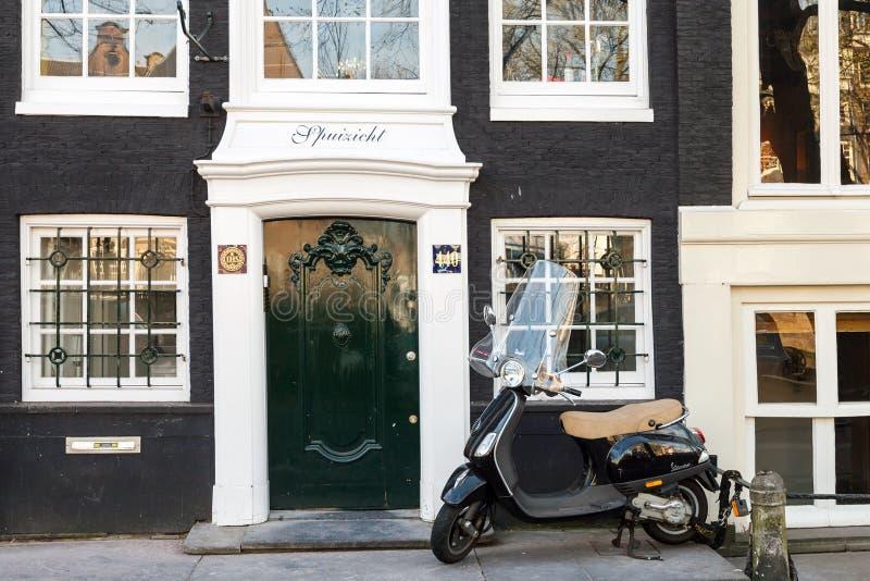 大黄蜂类滑行车在阿姆斯特丹站立停放在老生存房子附近 免版税库存照片