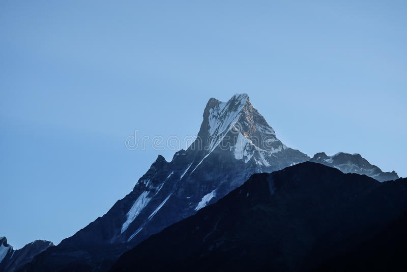 天、登上Machhapuchchhre和摆尾峰顶的前光 免版税库存照片