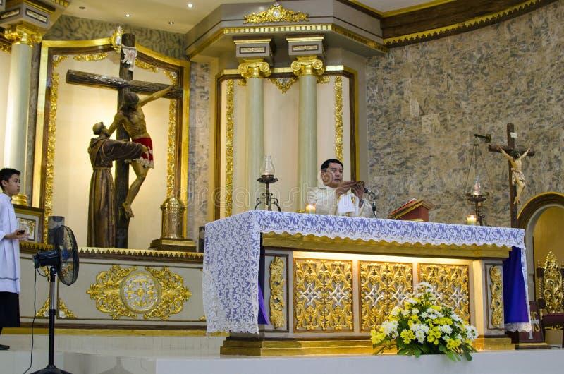 天主教教士庆祝会众讲道大量在教堂法坛 免版税图库摄影