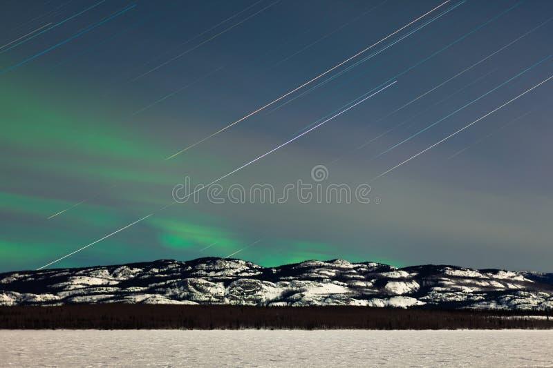 星足迹和在月亮的北极光点燃了夜 库存照片