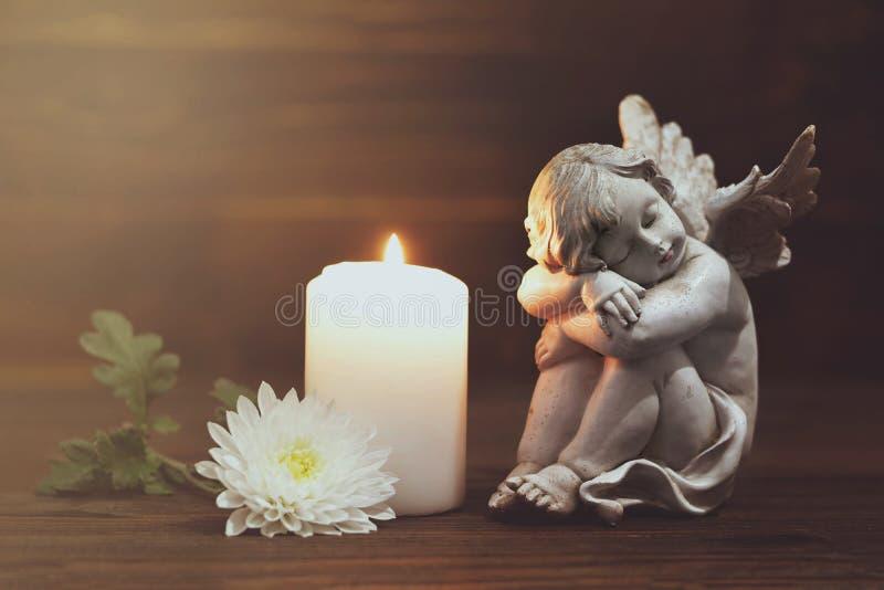 天使、白花和燃烧的蜡烛 免版税库存图片