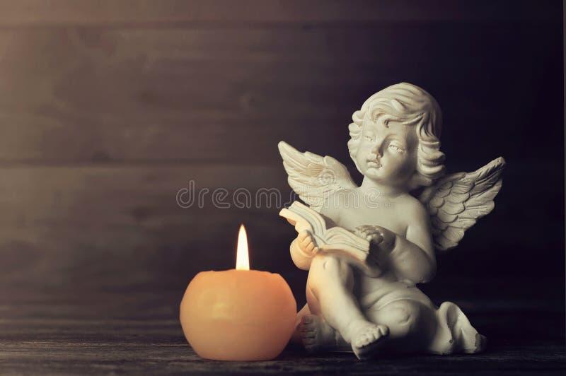 天使和白色蜡烛在黑暗的背景 库存图片
