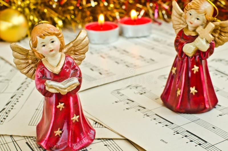 天使圣诞节小雕象在音乐纸张的 免版税库存图片