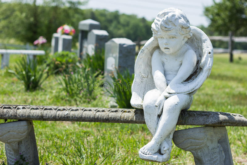天使坐石长凳在公墓 免版税库存照片