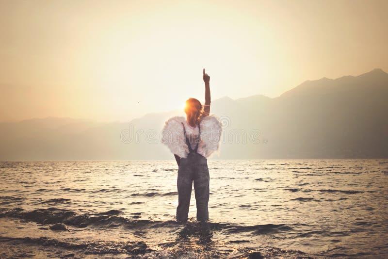 天使妇女接触的不可思议的片刻与手指的天空 免版税图库摄影