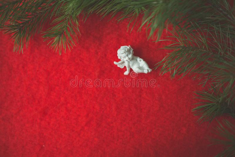 天使小雕象坐倾吐的小卵石和红色羊毛布料 库存图片