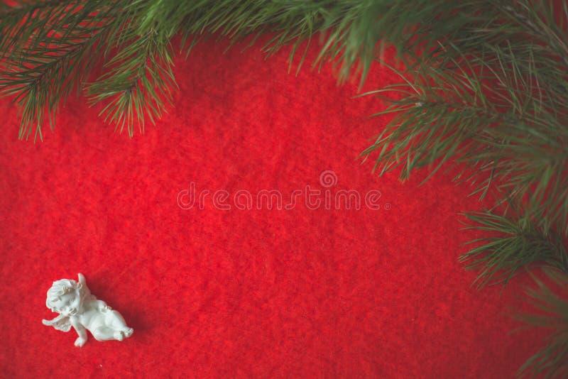 天使小雕象坐倾吐的小卵石和红色羊毛布料 图库摄影