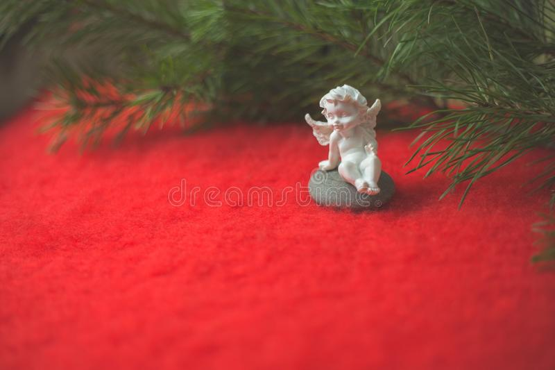 天使小雕象坐倾吐的小卵石和红色羊毛布料 免版税库存照片