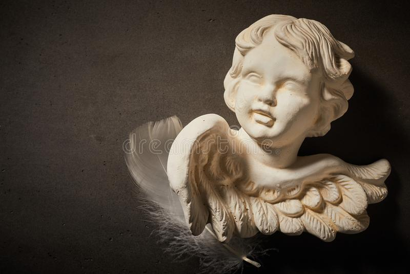 天使小雕象的纪念概念有羽毛的 库存照片