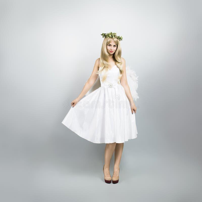 天使服装的少妇在灰色背景 免版税库存照片