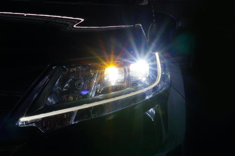 天使注视氙车灯发光的光学透镜 免版税图库摄影